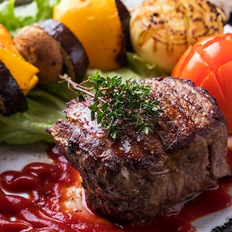Steak de bœuf. sauce rouge juteuse de steak de boeuf moyen et légumes grillés. fermer