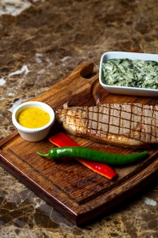 Steak de boeuf servi avec un mélange de yogourt et d'herbes, poivrons rouges et verts