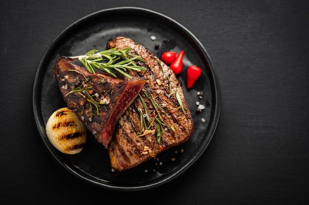 Steak de boeuf. steak de boeuf moyen au poivron rouge, herbes aromatiques et oignon frit
