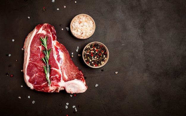 Steak de boeuf t-bone cru avec des épices sur la pierre de fond. avec espace de copie pour votre texte.