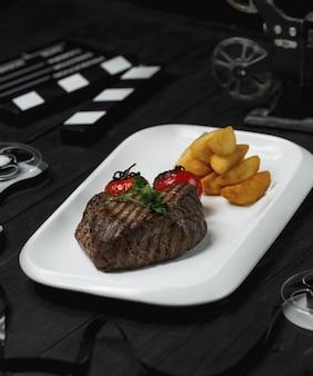 Steak de boeuf avec tomates grillées et pommes de terre frites.