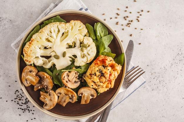 Steak de chou-fleur avec champignons et houmous grillés, vue de dessus.