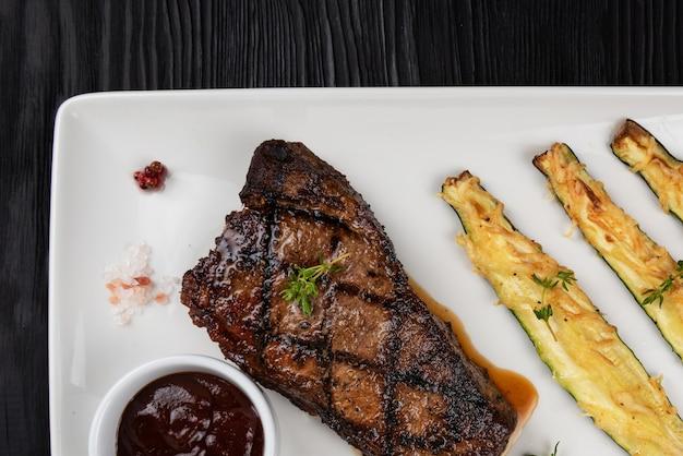 Steak de contre-filet black angus grillé new york avec courgettes sur plaque blanche sur fond en bois noir...