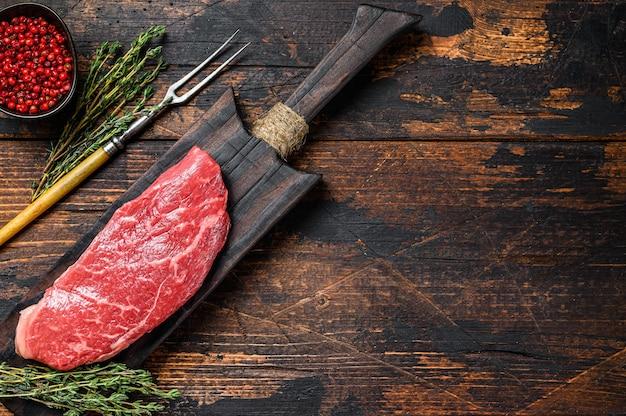 Steak de contre-filet cru sur une planche à découper, bœuf marbré. fond en bois foncé. vue de dessus. copiez l'espace.