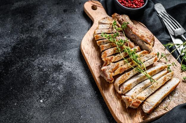 Steak de côte de porc grillé. viande biologique. fond noir. vue de dessus. espace copie