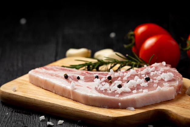 Steak de côtelette de porc cru sur la surface en bois sombre.