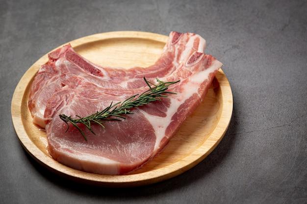 Steak de côtelette de porc cru sur la surface sombre.