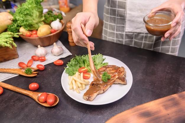 Steak de côtelette de porc maison avec salade. apprentissage en ligne pour cuisiner un régime et des aliments sains lorsque vous restez à la maison pendant le coronavirus.