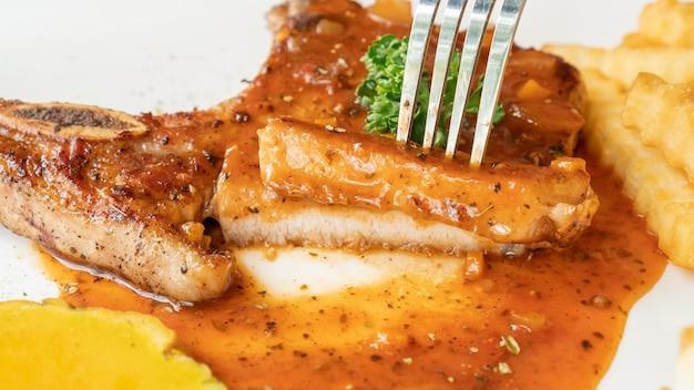 Steak de côtelette de porc sur une plaque blanche.