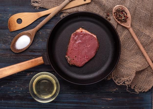 Steak cru dans une poêle à frire, huile, sel et poivre dans une cuillère en bois sur fond de bois