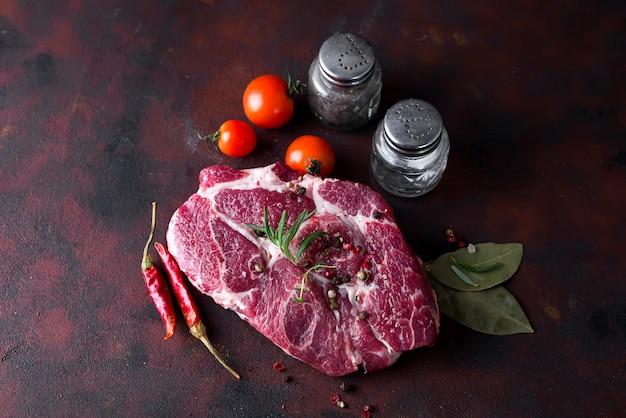 Steak cru avec des épices et des ingrédients pour la cuisson.