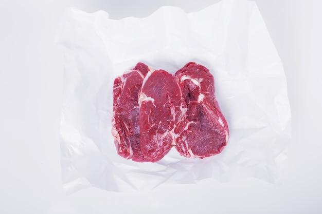 Steak cru sur papier blanc