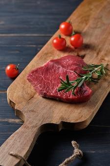 Steak cru sur une planche de bois, garni de tomates cerises et d'un brin de romarin.