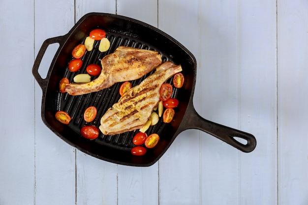 Steak cuit dans une poêle en fer sur une surface en bois