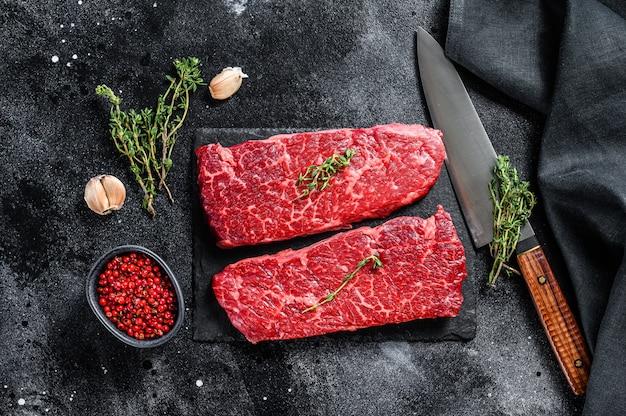 Steak denver cru sur une planche de pierre avec des herbes