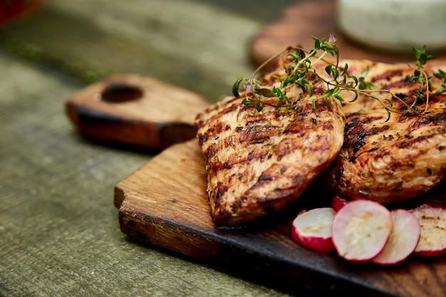 Steak dinde grill sur une planche à découper en bois avec une variété de légumes grillés rustiques