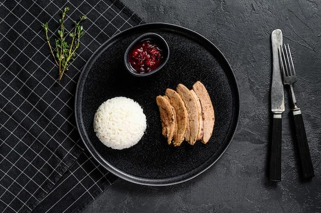 Steak de dinde grillé avec un accompagnement de riz. fond noir. vue de dessus. espace pour le texte