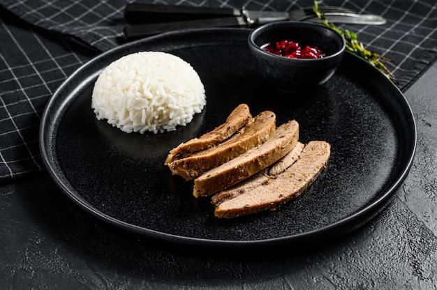Steak de dinde grillé avec un accompagnement de riz. fond noir. vue de dessus