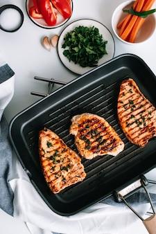 Steak de dinde grillé aux herbes et épices dans une poêle noire sur la table.