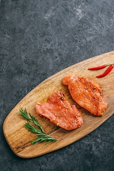 Steak de dinde mariné sur une planche de bois avec du romarin et du piment, copiez l'espace.