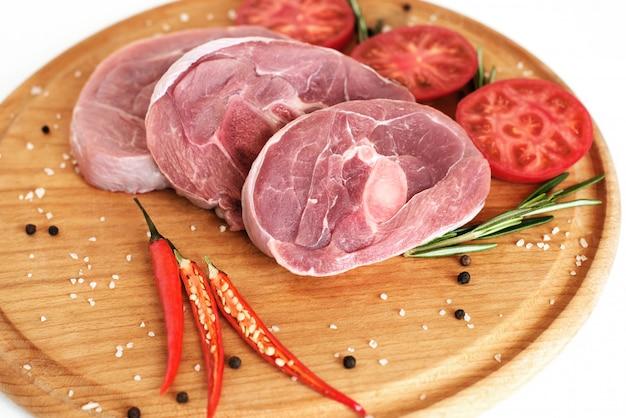 Steak de dinde, trois morceaux de viande sur une planche de bois, avec du poivre et des tomates