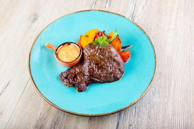 Steak de faux-filet avec moutarde et légumes grillés sur une assiette vue de dessus