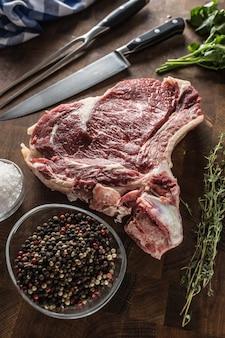 Steak de faux-filet avec os sur planche de boucher avec fourchette et couteau aux herbes sel poivre.