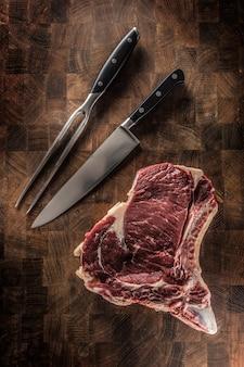 Steak de faux-filet avec os sur planche de boucher avec fourchette et couteau.
