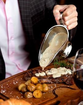 Steak de faux-filet avec pommes de terre frites sous une sauce aux champignons
