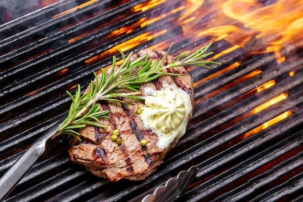 Steak sur un feu de gril, avec des herbes et du beurre