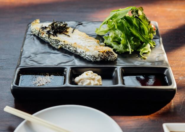 Steak de filet de bar japonais servi avec salade, mayonnaise et sauce shoyu.