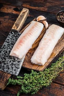 Steak de filet de morue cru sur planche de bois avec couperet de boucher. fond en bois foncé. vue de dessus.