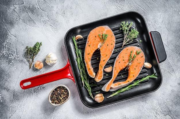 Steak de filet de saumon dans une poêle. poisson frais cru. fond blanc. vue de dessus.