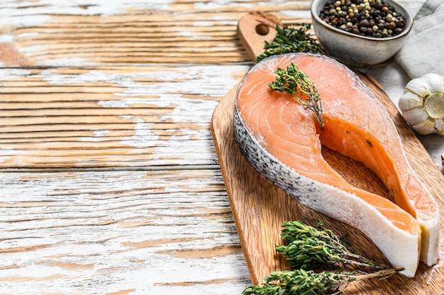 Steak de filet de saumon sur une planche à découper. poisson biologique cru. fond blanc. vue de dessus. copiez l'espace.