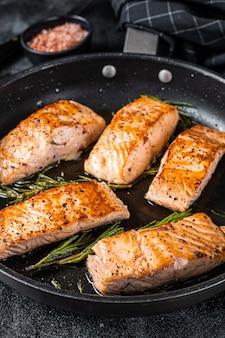 Steak de filet de saumon rôti dans une poêle au romarin. fond noir. vue de dessus.