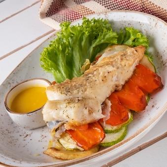 Steak de flétan aux légumes sur une assiette