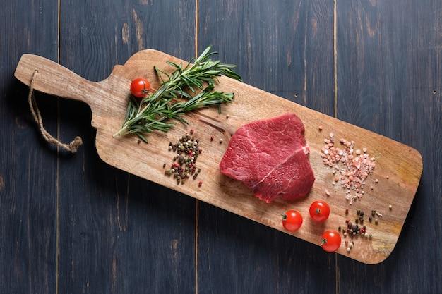 Steak fraîchement cuit tranché avec du sang, servi sur des branches de romarin frais sur une planche de bois