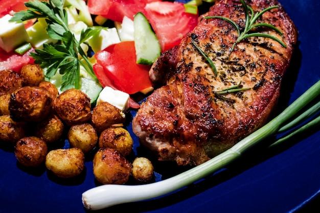 Steak frit appétissant avec pommes de terre frites salade grecque et oignons verts sur une assiette bleue