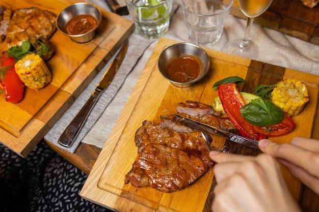 Steak grillé contre-filet et sauce au poivre sur une planche à découper sur fond de bois foncé.