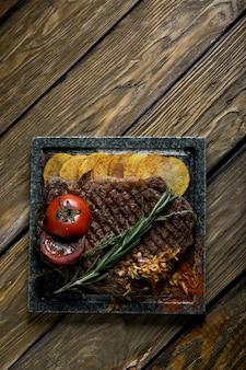 Steak grillé avec couteau et fourchette sculptés dans l'ardoise de pierre noire