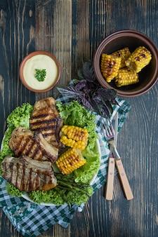 Steak grillé dans un bol rond avec des épices, des herbes et des légumes sur un bois foncé. .