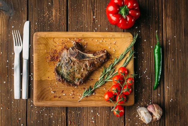Steak grillé juteux sur l'os, vue de dessus, personne. couteau et fourchette sur table en bois