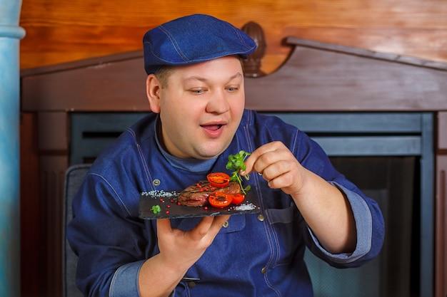 Steak grillé avec micro-verts et tomates sur une assiette carrée noire.