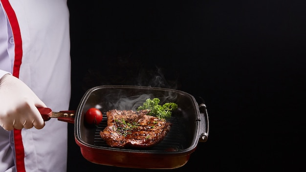 Steak grillé sur poêle avec chef cuisinier