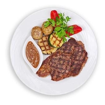 Steak grillé, pommes de terre au four et légumes sur plaque blanche isolée.