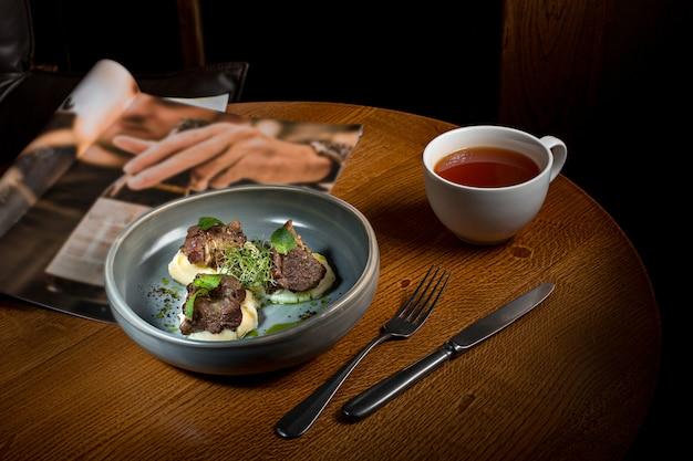 Steak grillé avec purée de légumes sur plaque sur table en bois.