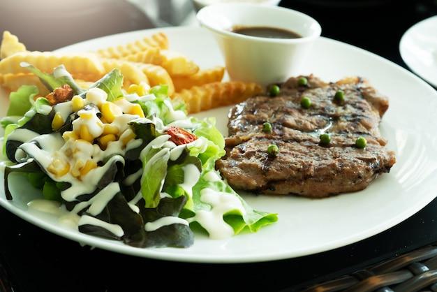 Steak grillé et salade de légumes avec pommes de terre frites. nourriture faite maison.