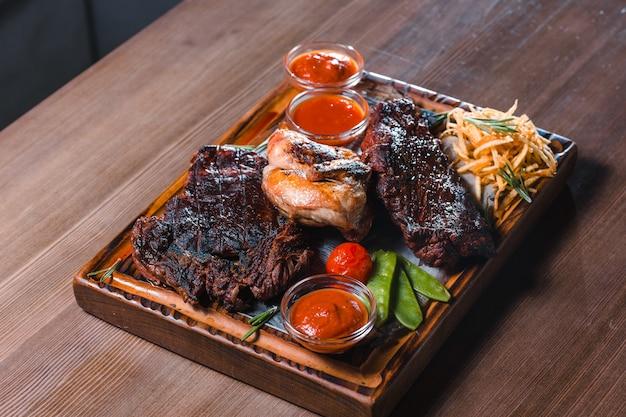 Steak grillé servi avec des légumes et des herbes décorés avec une serviette sur une planche en bois rustique
