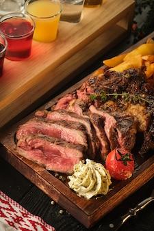 Steak juteux au beurre parfumé. steak de ribeye tranché avec pommes de terre, oignons et tomates cerises au four