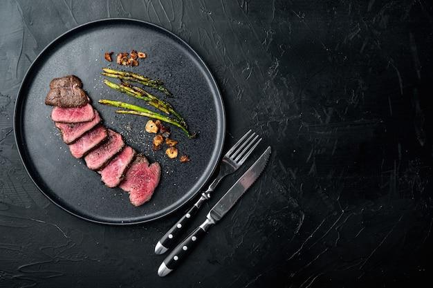 Steak juteux de bœuf saignant moyen filet mignon ou filet d'oeil, avec oignon et asperges, sur assiette, avec couteau et fourchette à viande, sur pierre noire